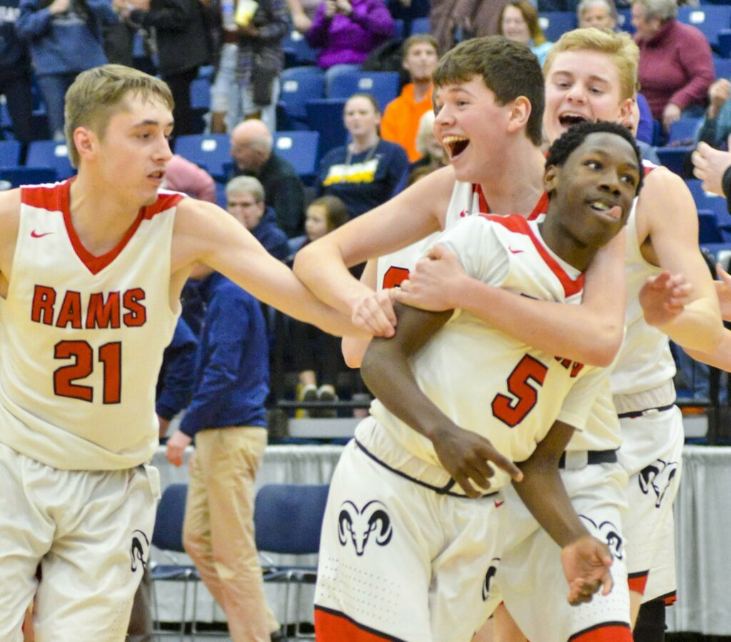 Cony players Bryan Stratton, left, and Luke Briggs run to hug Simon McCormick (5) after the Rams'  73-71 win over Medomak in the Class A North quarterfinals on Saturday at the Augusta Civic Center. McCormick's game winning layup put the Rams on top with seven seconds remaining.
