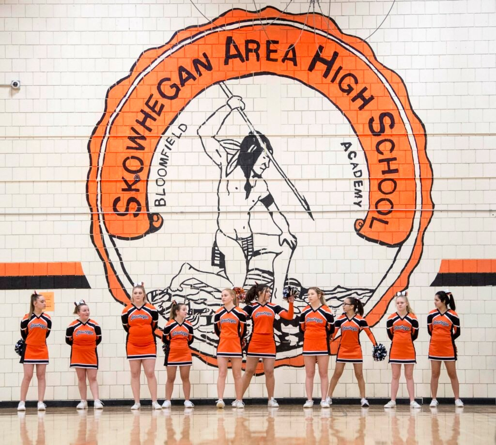Skowhegan Area High School cheerleaders stand on Jan. 15 beneath the Indian mural on the wall of the school's gymnasium.
