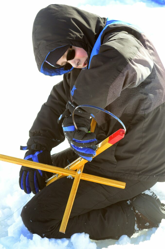 After his trap's flag was tripped but there was no fish on the hook, Mcgyver Blundon resets the trap before putting it back into a hole in the ice Saturday during a children's ice fishing derby on Cochnewagon Lake in Monmouth.
