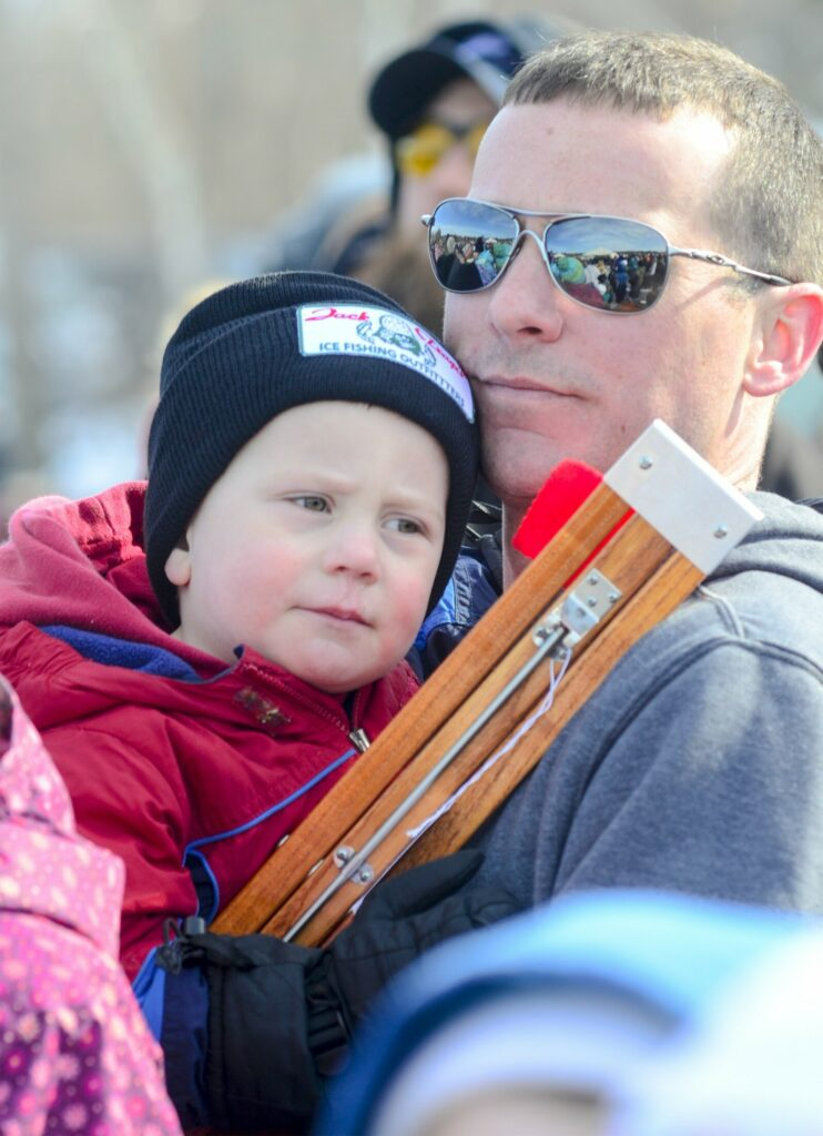 Brian Bailey holds his 3-year-old son, Sawyer Bailey, and the ice fishing trap that Sawyer won in a raffle at the children's ice fishing derby Saturday on Cochnewagon Lake in Monmouth.
