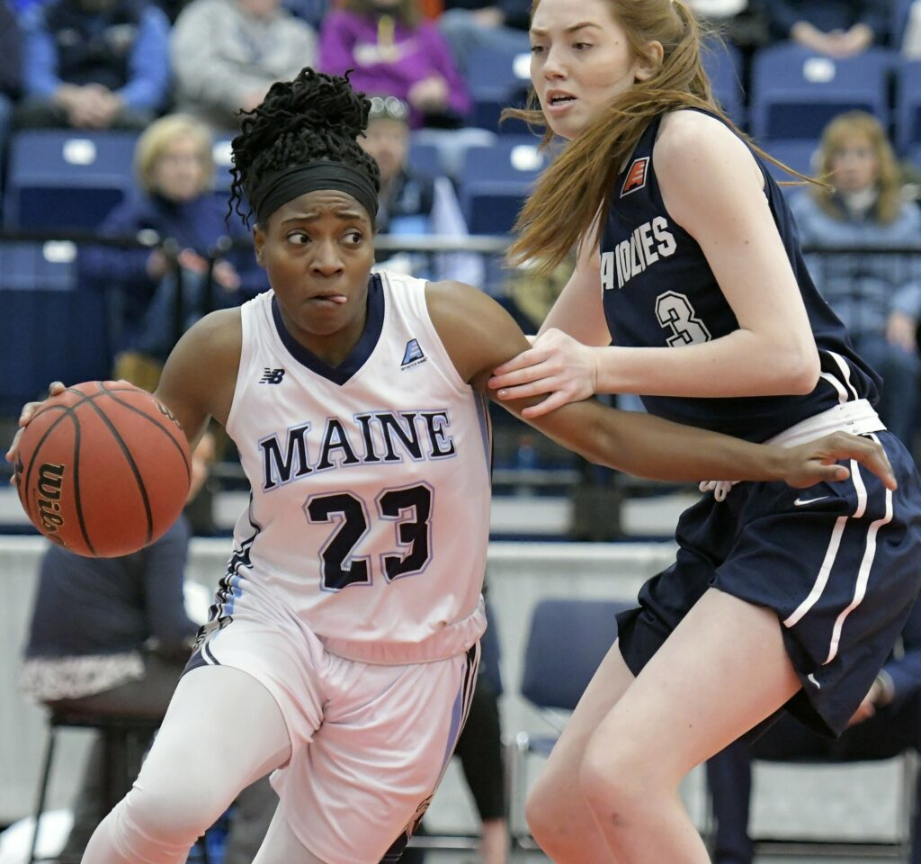 The University of Maine's Tanesha Sutton dribbles around State University of New York at Stony Brook's Oksana Gouchie-Provencher during a basketball game Sunday at the Augusta Civic Center.