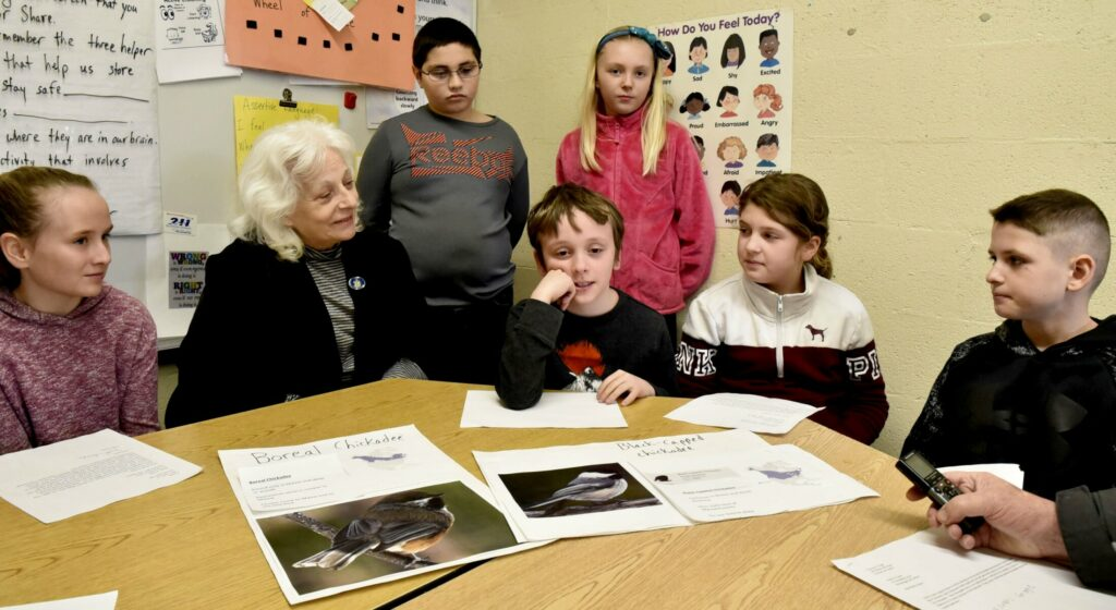 Margaret Chase Smith student Jasiah Marshall, center, explains why he would like the boreal chickadee, image at left, to be officially named the Maine state bird on Monday. Students in the fourth grade wrote letters that will accompany state Rep. Betty Austin when she proposes the law this week in Augusta. From left are Faith Pease, Austin, Thomas Gage, Marshall, Addie Bubier, Emilee Kirby and Evan Goodridge.