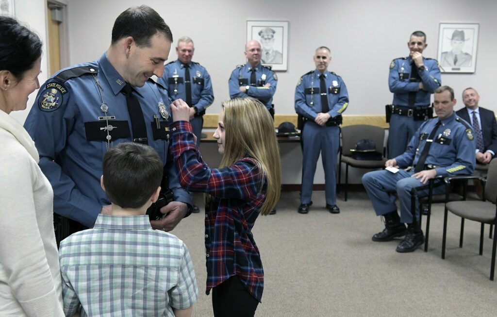 Braelyn Hood, 12, pins a Maine State Police lieutenant's badge on the chest of her father, Patrick Hood, during a promotion ceremony Monday at the Department of Public Safety in Augusta. Hood was elevated to oversee Troop D — an area that includes Knox, Sagadahoc, Lincoln, Waldo and portions of Kennebec County. Hood has served his entire 21-year career in Troop D, both as a patrol officer and sergeant, and will oversee 22 troopers. Hood replaces Lt. Aaron Hayden, who is assuming the command of the Truck Weights section of the State Police. Hood was joined by his wife, Mandy, left; son, Wyatt, 9; and the entire command staff of Public Safety, at rear.