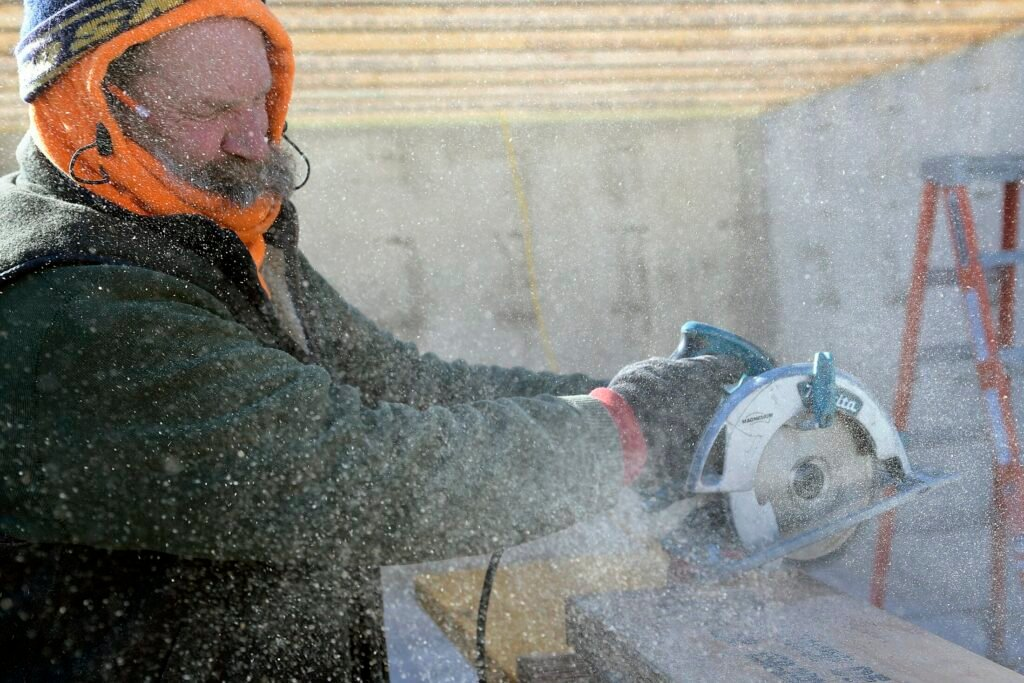"Brad Ellis cuts beams on Tuesday in 25 mph wind at a home that his firm, BHS Inc., is building in Farmingdale. Ellis said the work continues with his crew despite the frigid conditions since he has several months of work booked. ""You get it done,"" he said."