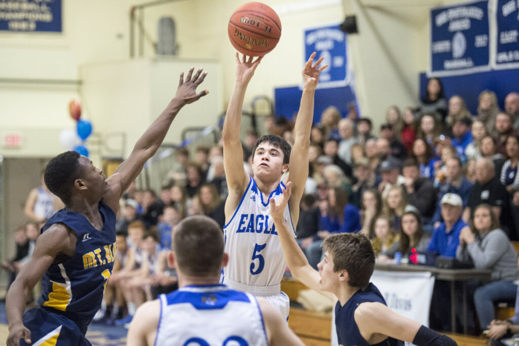 Erskine's Caden Turcotte (5) takes a shot as Mt. Blue's James Anderson, left, and Jacob Farhnam defend during a Class A North game Tuesday night in South China.
