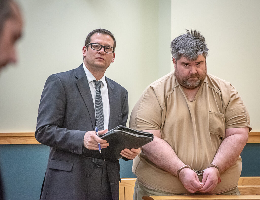 Steven Downs, 44, of Auburn, right, stands for his initial appearance in 8th District Court in Lewiston on Feb. 19. Downs has been charged with the 1993 rape and murder of 20-year-old Sophie Sergie at the University of Alaska Fairbanks. Standing with Downs is attorney Richard Charest.