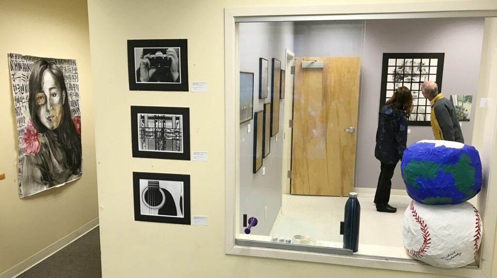 Showgoers look at a self-portrait by Maranacook Community High School student Ruslan Reiter on April 28, 2017, during Raw Space Augusta Art Walk in downtown Augusta. The exhibition was a pop-up event that showcased visual and performing arts in downtown Augusta's vacant storefronts and offices.