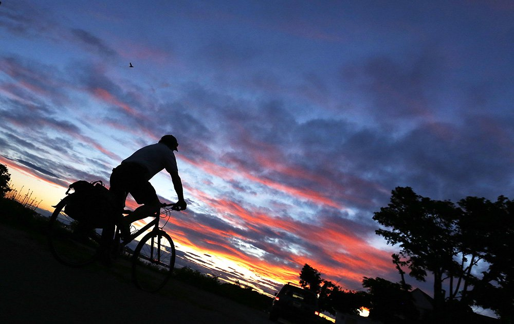 Walter Reiter rides his bike to a lookout spot on Island Avenue on Peaks Island Wednesday to catch the last light of the sunset on summer solstice. Staff photo by Ben McCanna