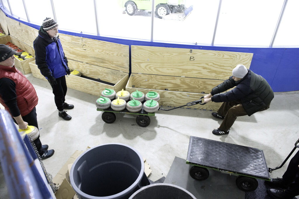 Nick Matluck of Freeportpulls curling stones out of storage at the William B. Troubh Ice Arena in Portland recently. Each stone weighs 42 pounds.