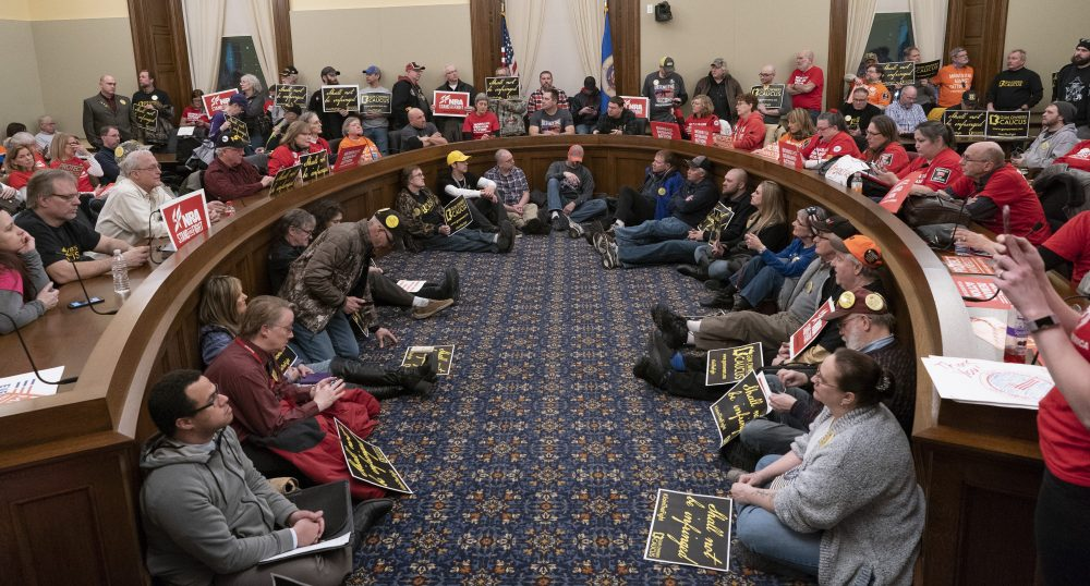 """The overflow room was full as supporters on both sides listened as the House public safety committee talked about two bills that would expand background checks and adopt a """"red flag"""" law at the State Capitol Wednesday, Feb. 27, 2019, in St. Paul, Minn. The Minnesota House committee has voted to require universal criminal background checks for gun purchasers. (Jerry Holt/Star Tribune via AP)"""