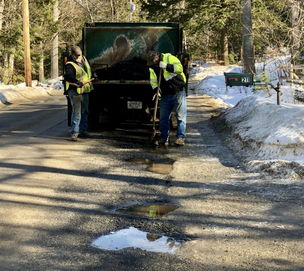 Winthrop Public Works employees David Boucher, left, and Gary Vigue patch holes Tuesday on Memorial Drive in Winthrop.
