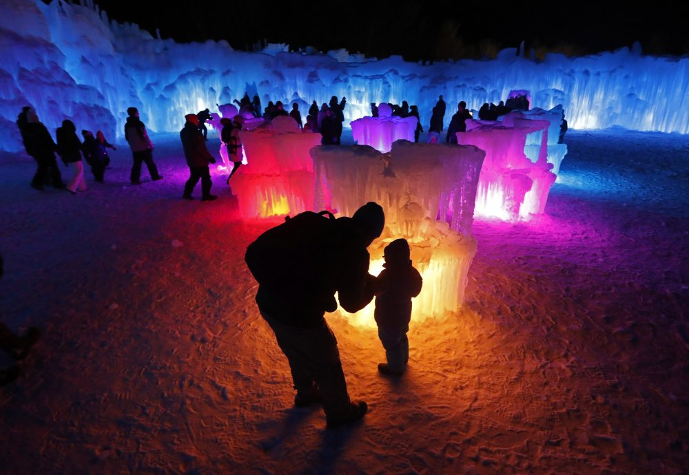 In this Saturday, Jan. 26, 2019 photo, Bruce McCafferty and his son, Dougie, pause while exploring the ice formations growing at Ice Castles in North Woodstock, N.H.