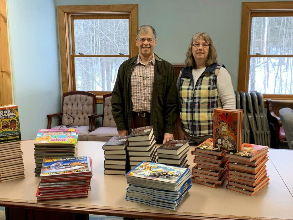 Carol Eckert's husband, Jeff Frankel, left, and Julie Bailey, project organizer, with the 120 volumes recently donated to Carol's Corner by Scholastic.