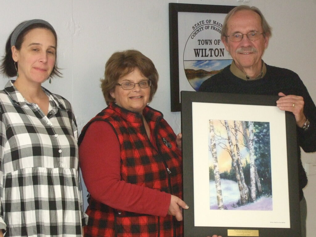Jen Jespersen, left, president of the Maine Lakes Society, with Rhonda Irish, Wilton town manager, accepting the painting from Rob Lively.
