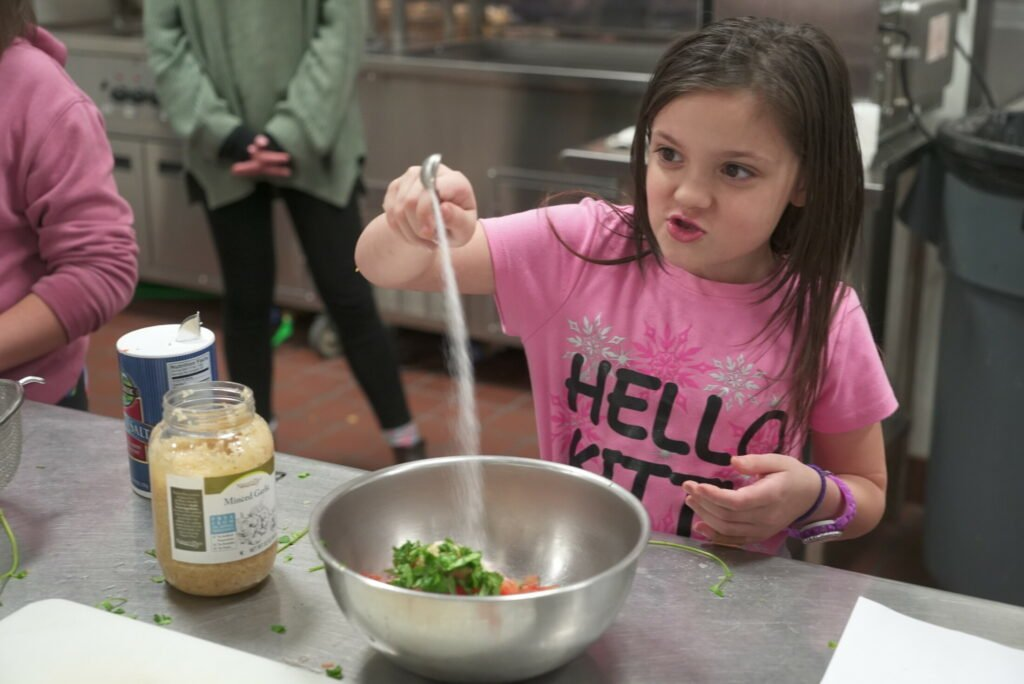 Lexi Lepage, at student at the Albert S. Hall School in Waterville, adds salt to her pico de gallo during the Sprout Scouts' field trip to the Mid Maine Technical Center in Waterville. Lexi is a member of her school's Sprout Scouts where they learn about cooking and gardening.