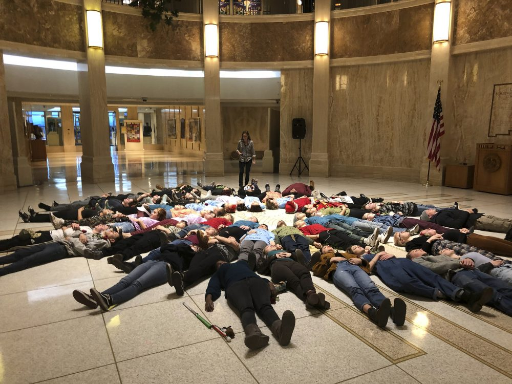 "Student advocates for new gun safety regulations hold a silent ""lie-in"" protest in the state Capitol in Santa Fe, N.M., on Wednesday, Feb. 13, 2019, in anticipation of the anniversary Thursday of the mass shooting at Marjory Stoneman Douglas High School in Parkland, Fla. Some wore T-shirts bearing the names of individuals killed in Parkland. The New Mexico House of Representatives was poised to vote on a bill that would make it easier to take guns away from people who may be suicidal or bent on violence. (AP Photo/Morgan Lee)"