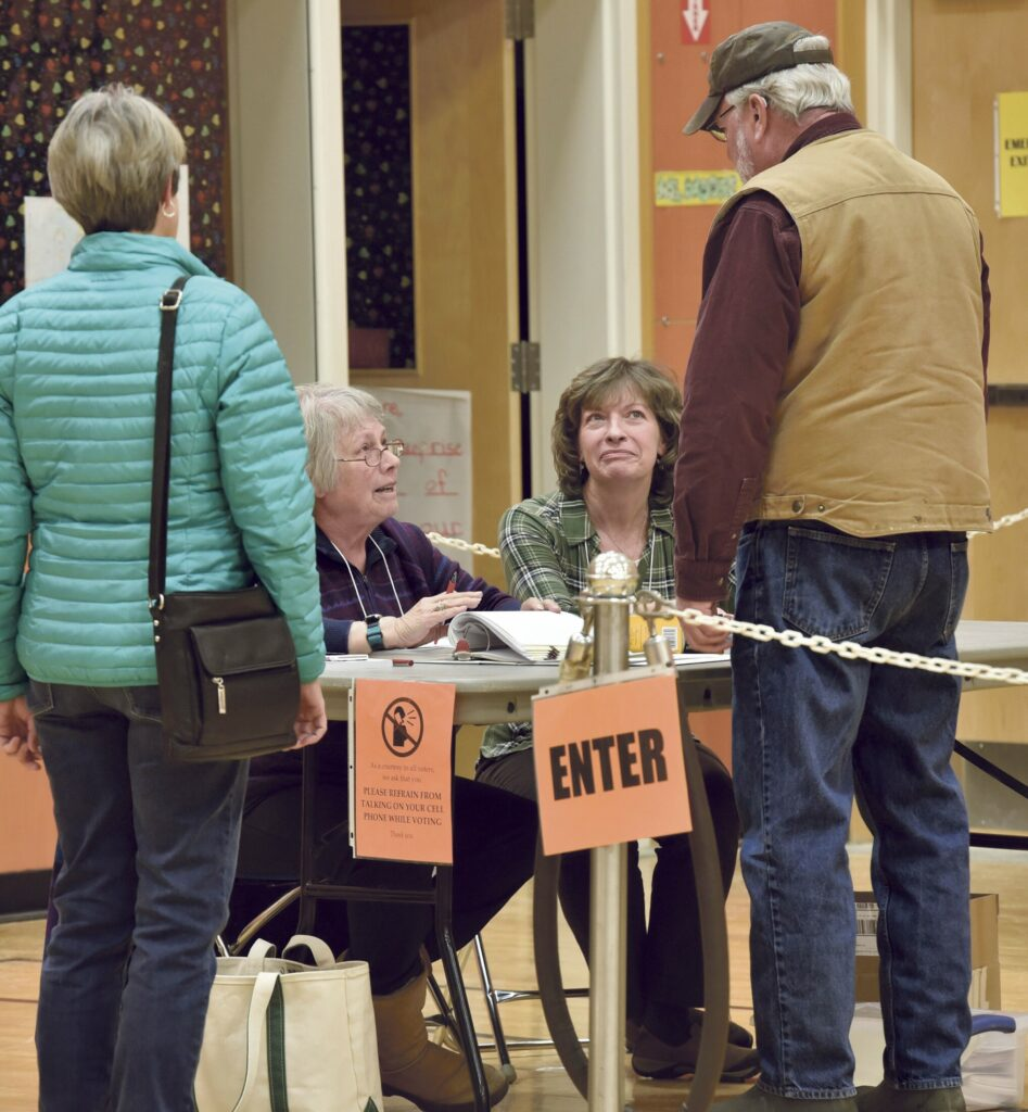 Norridgewock election clerks Kay Laney, seated at left, and Kelly-Ann Withee, speak with voters Gail and Jack Gibson before they vote at the Mill Stream School prior to the annual Town Meeting on Monday.