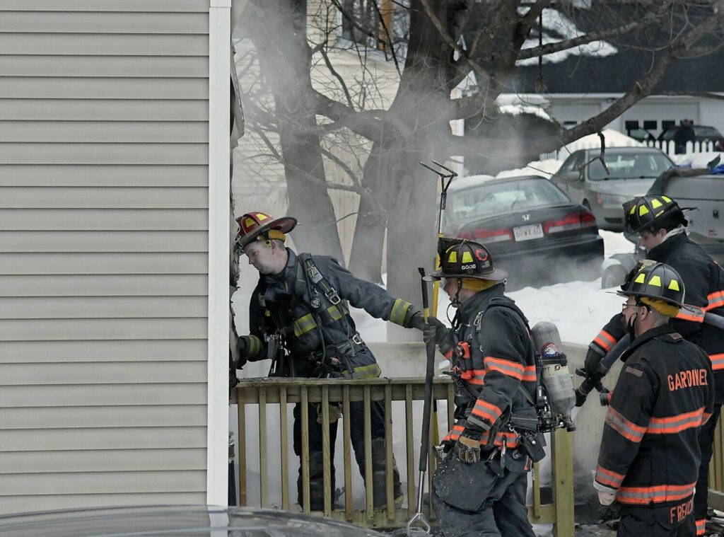Firefighters extinguish hot spots Feb. 27 on an exterior wall of a Highland Avenue residence that caught fire in the early afternoon in Gardiner.
