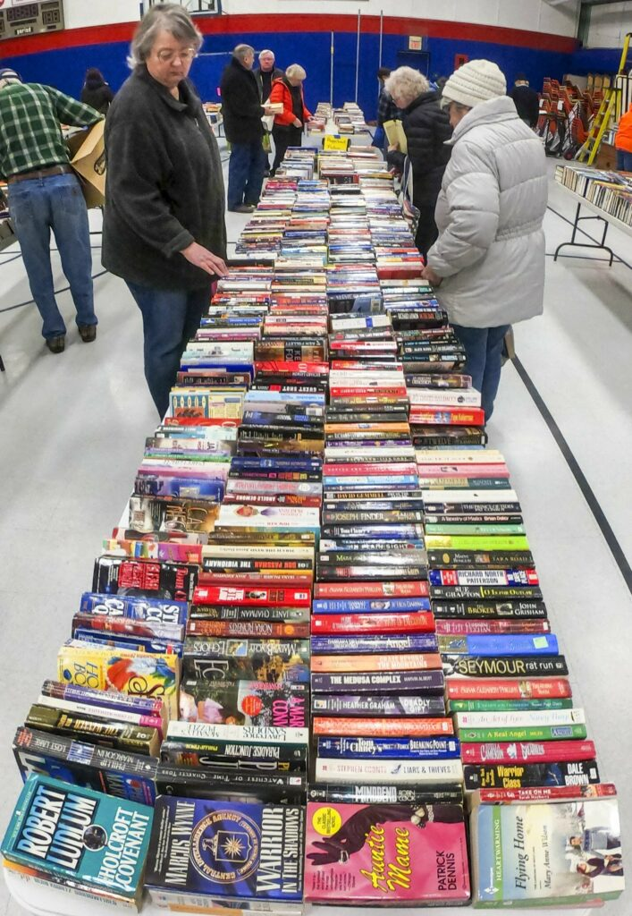 Shoppers browse among the tables Saturday during the Friends of the Belgrade Library book sale in the Belgrade Central School gymnasium.