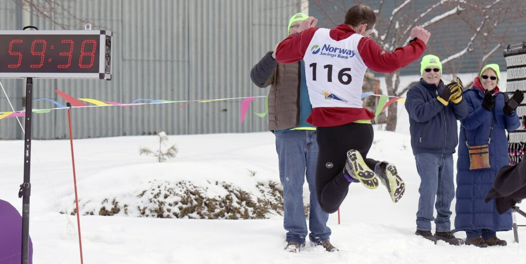 Stephen Judice, of Dayton, celebrates finishing first, in under an hour, Sunday during the triathlon held at the Meadows Golf Club in Litchfield. Competitors from several states and across Maine skied, shoed, ran and biked for several miles.