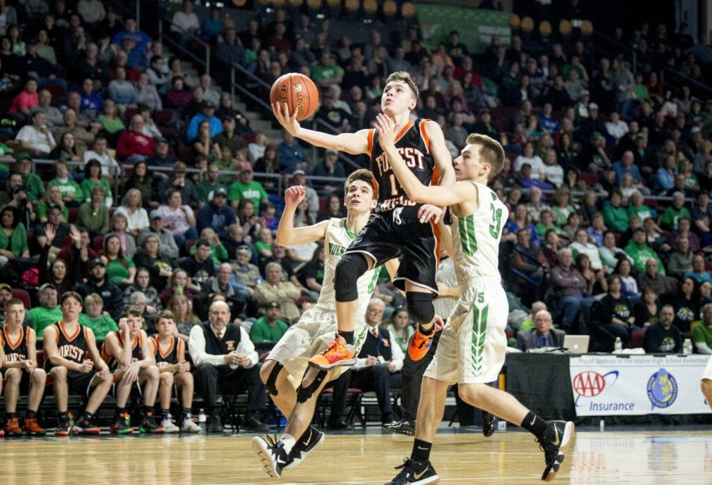 Forest Hills' Parker Desjardins (14) drives to the basket as  Schenk's Andrew Goula defends during the Class D state championship game last season at the Cross Insurance Center in Bangor.