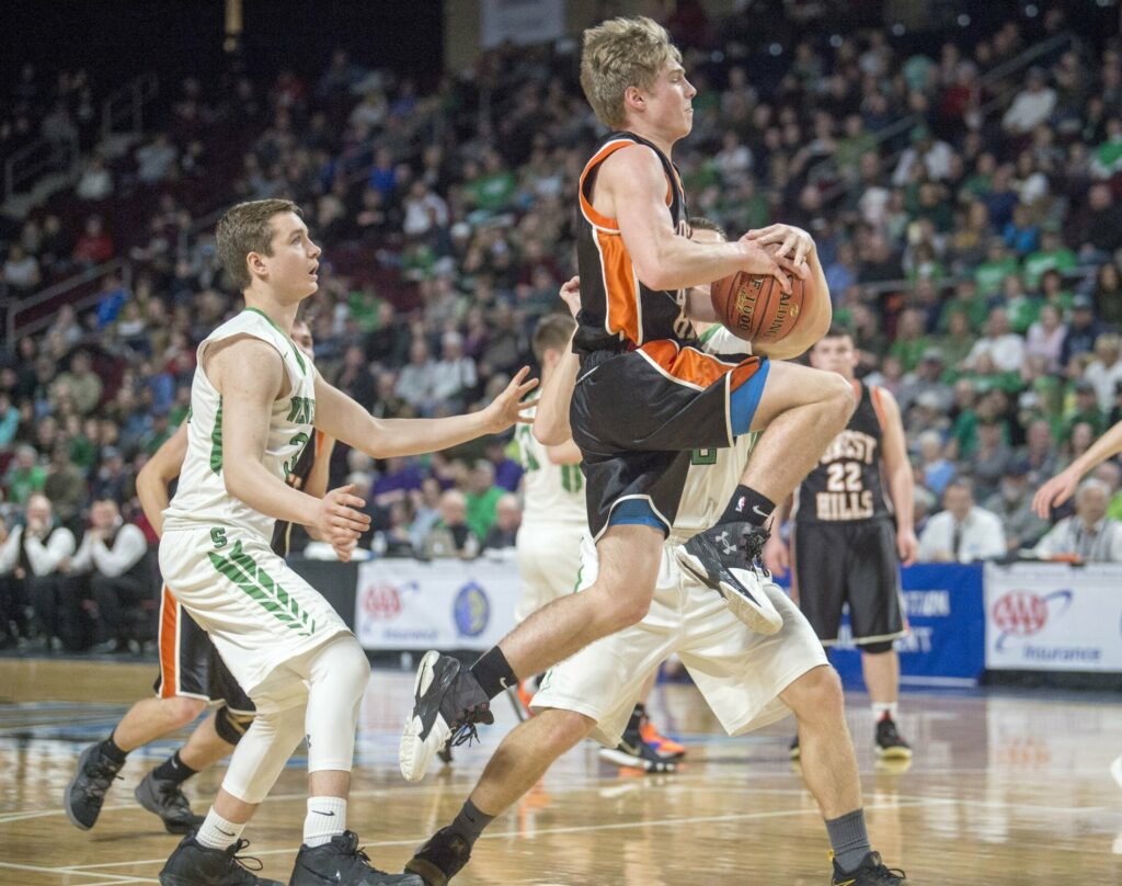 Forest Hills' Dalton Gregoire draws the foul from Schenk's Travis Thompson in the Class D state championship game Saturday at the Cross Insurance Center in Bangor.