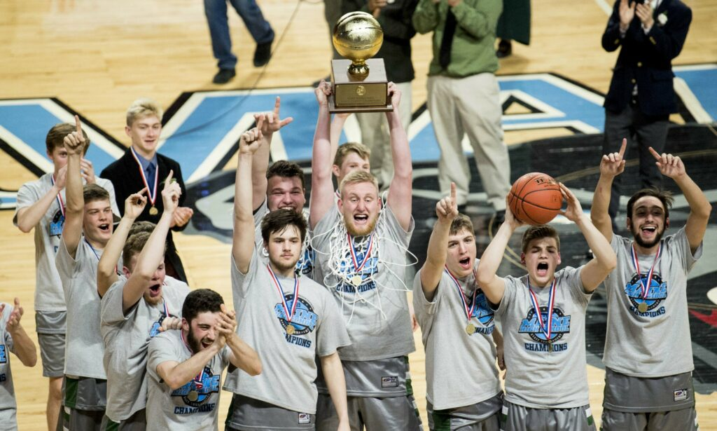 Winthrop senior Cam Wood, center, hoists the Gold Ball over his head to celebrate the team's Class C state title Saturday night in Bangor.