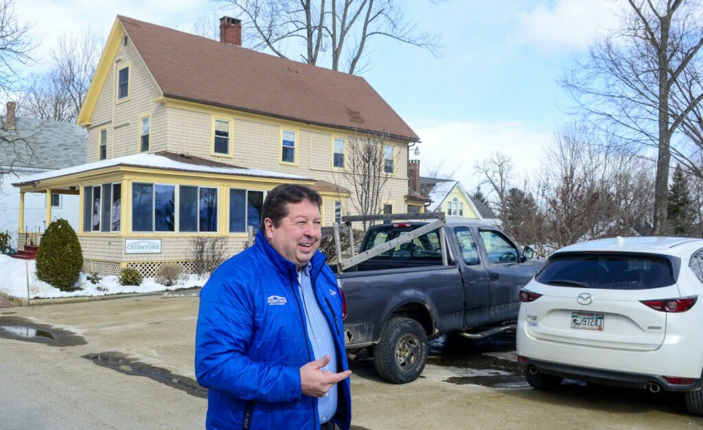 Scott Upham, managing partner of Cribstone Capital Management, talks about the parking controversy near his office, in background, on Thursday on North Chestnut Street in Augusta.