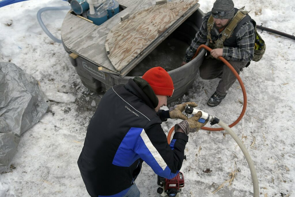 Nathan Bacon, left, and Tyler Jepson pump sap Sunday at the Bacon Farm Maple Products sugar bush in Sidney.