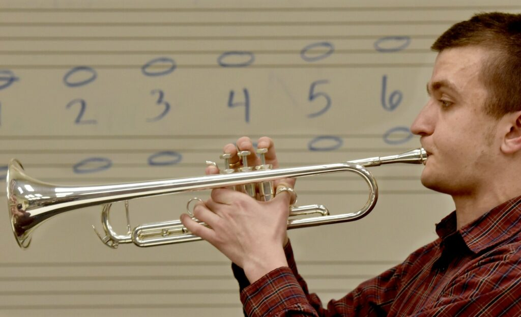 """Lawrence High School senior Nathanael Batson plays his trumpet in front of a board scripted with whole notes on Thursday. Batson is the recipient of the 2019 Section 1 """"Heart of the Arts"""" award. He is legally blind and memorizes the music he plays."""