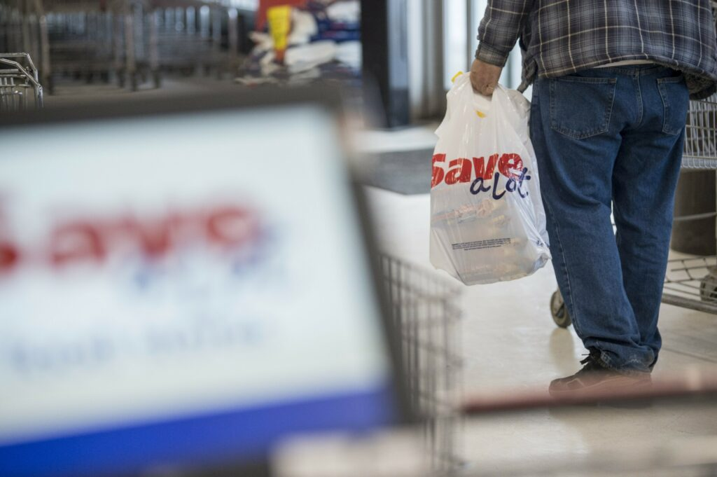 A shopper leaves with a plastic bag, purchased for an additional 10 cents, from Save-a-Lot in Waterville on Friday.