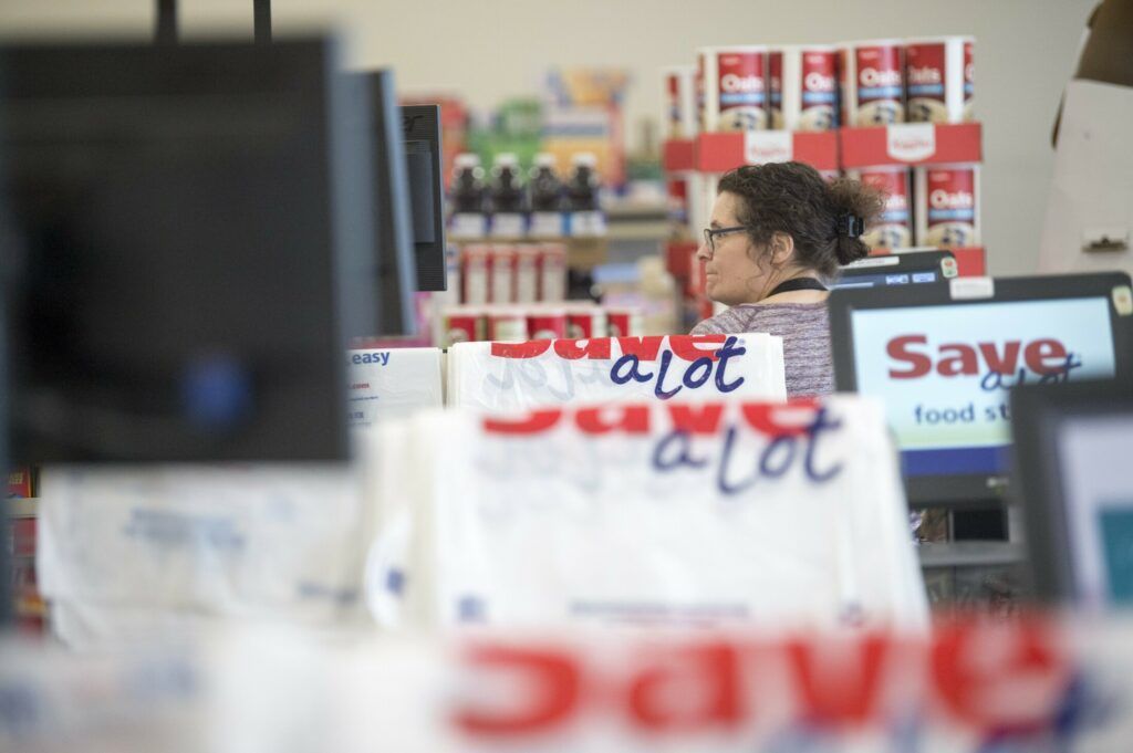 Margaret Withee, a cashier at Save-a-Lot, stands at her register with plastic bags that cost 10 cents each draped over the register partitions at Save-A-Lot in downtown Waterville on March 15.