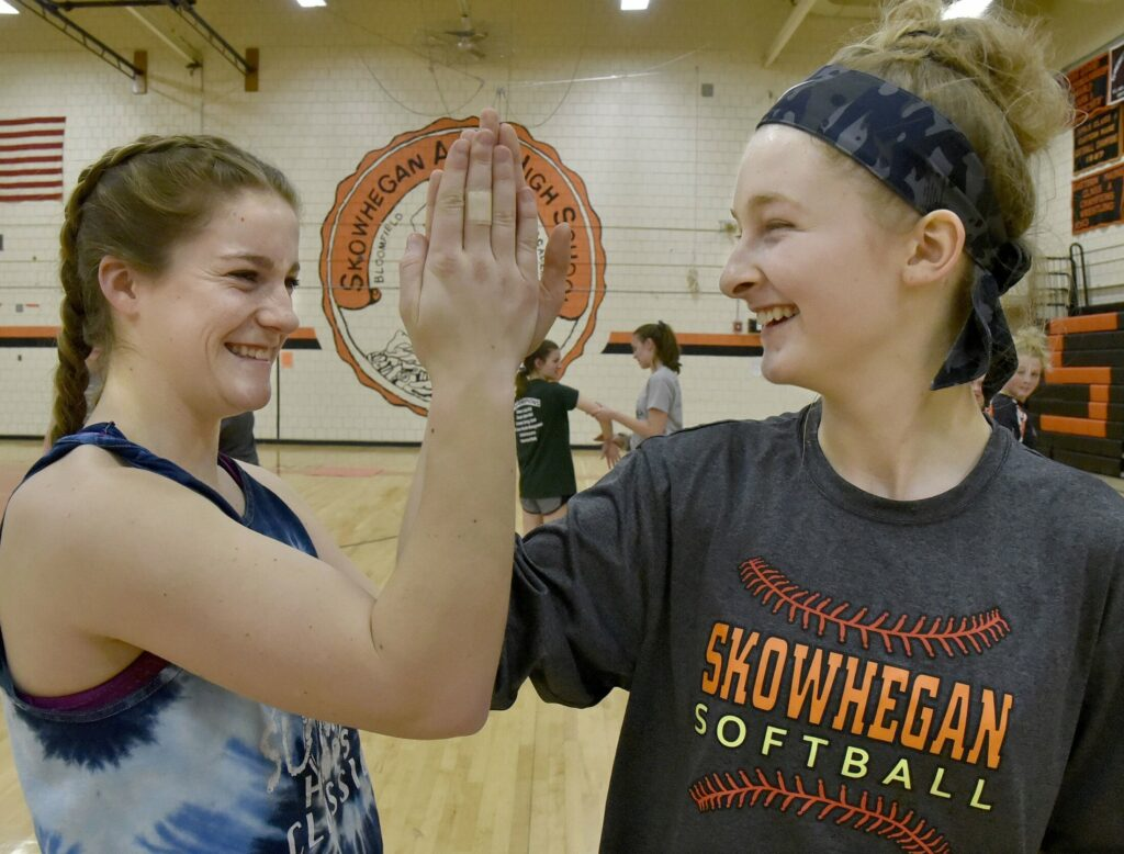 Skowhegan pitcher Sydney Ames, left, and catcher Sydney Reed share a laugh in the school's gymnasium during a preseason practice.