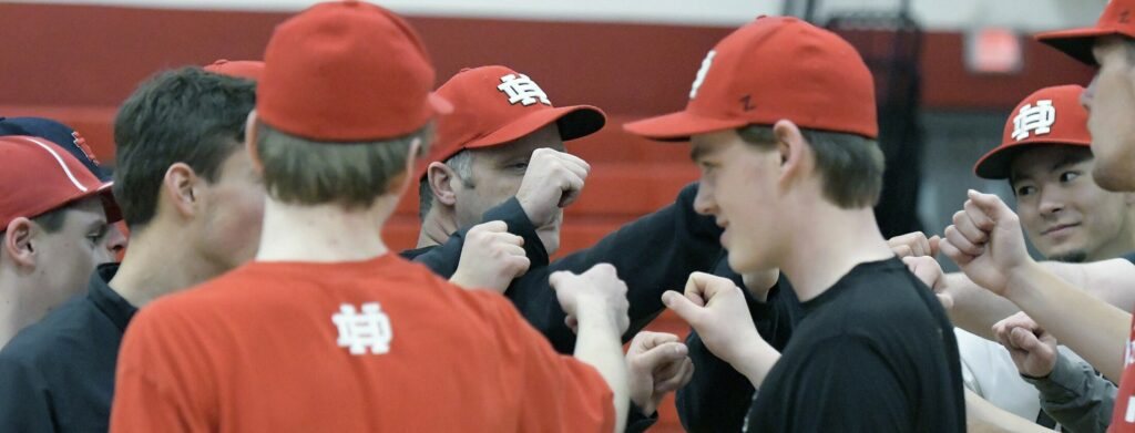 Hall-Dale High School pitchers and catchers knock knuckles during a preseason practice in Farmingdale..