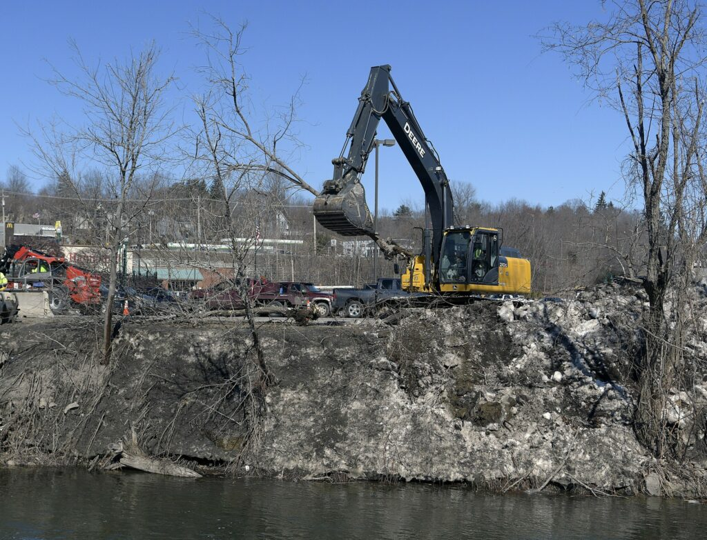 Invasive trees are removed Monday from the banks of Cobbosseecontee Stream in Gardiner as part of the the Department of Transportation project to replace two bridges crossing the stream.