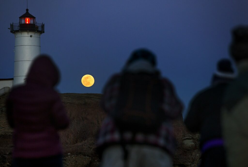 Photographers gather on the rocks at Sohier Park in York as they aim to capture the moonrise over Nubble Light.