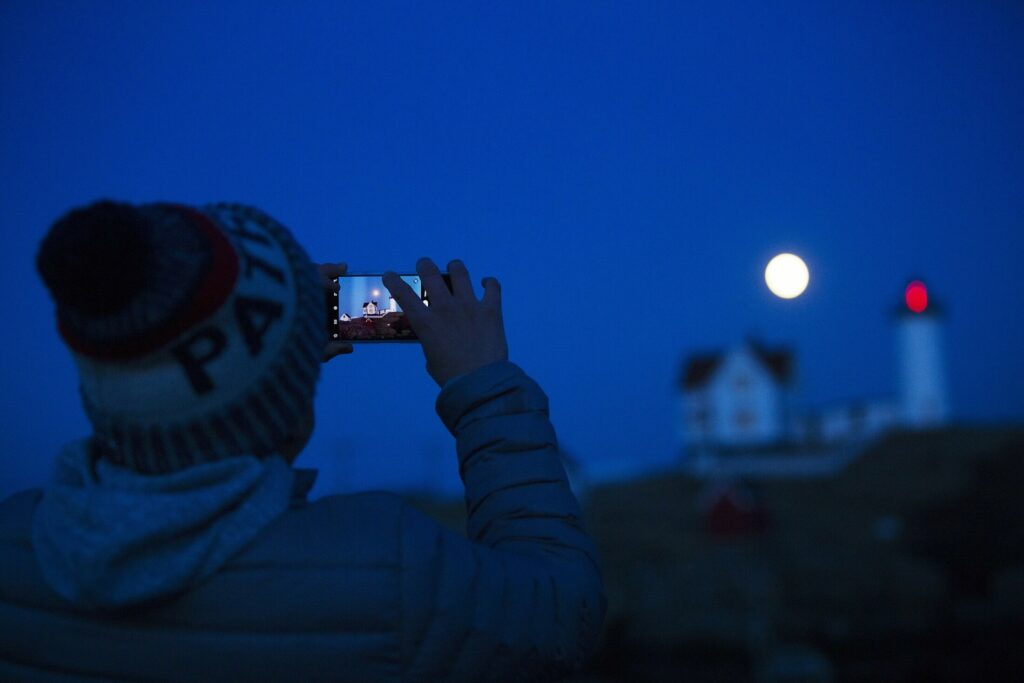 Michael Cabelin of York takes a photo of a full moon rising over Nubble Light on March 20.