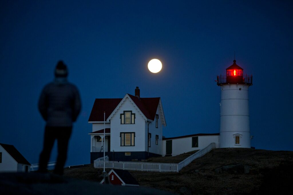 Michael Cabelin of York watches a full moon rising over Nubble Light on March 20.