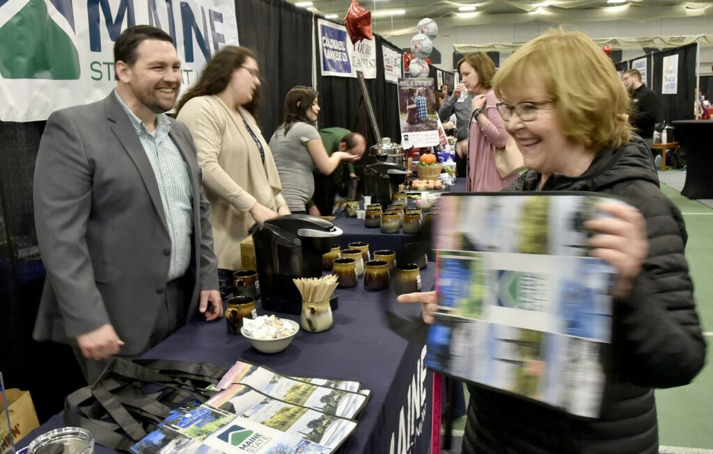 Bruce Harrington, of Maine State Credit Union and chairman of the Business to Business Showcase committee, gives away a reusable bag to a patron of the event, held Thursday at Colby College in Waterville.