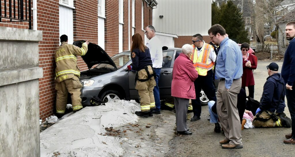 A conscious woman driver is treated at the scene after her vehicle struck the side of the Blessed Hope Church in Waterville on Sunday.