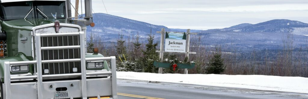 Trucks pass the scenic Jackman town line sign surrounded by mountains on U.S. Route 201 on Jan. 22, 2018. Elections are scheduled for Wednesday and Town Meeting is to be held Thursday.