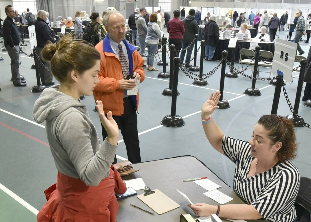 Colby College student Alexandria Fraize, left, swears the information she gave election clerk Allison Brochu is accurate before voting at Thomas College on Tuesday, Nov. 6, 2018. City Solicitor Bill Lee observes. After an effort to disqualify the votes of Colby College students in the November election was dismissed by the Maine Supreme Judicial Court, an appeal has been lodged with the city of Waterville's Voter Registration Appeals Board.