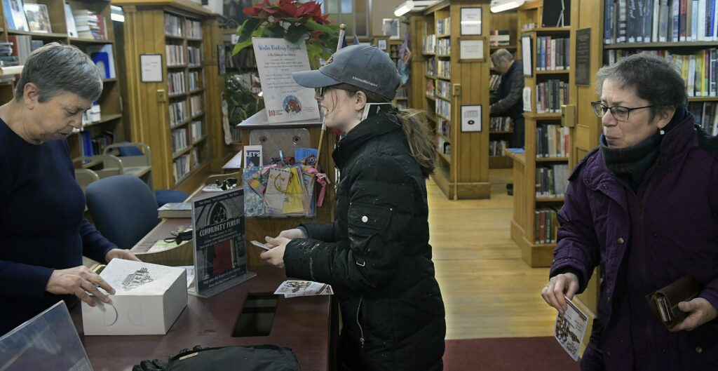 Patrons talk at the front desk at Hubbard Free Library on Jan. 24 in Hallowell.
