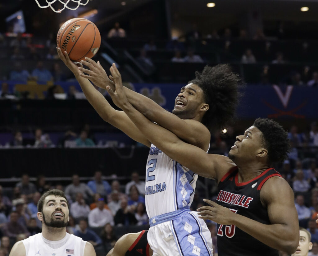 North Carolina's Coby White (2) drives past Louisville's Steven Enoch (23) during the first half of an NCAA college basketball game in the Atlantic Coast Conference tournament in Charlotte, N.C., Thursday, March 14, 2019. (AP Photo/Chuck Burton)