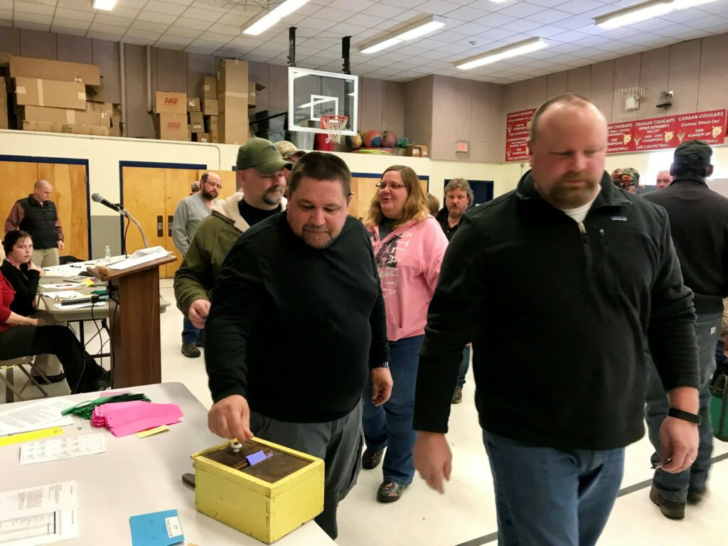 Canaan resident Ford Nelson, center, casts a ballot Saturday at Town Meeting at Canaan Elementary School.
