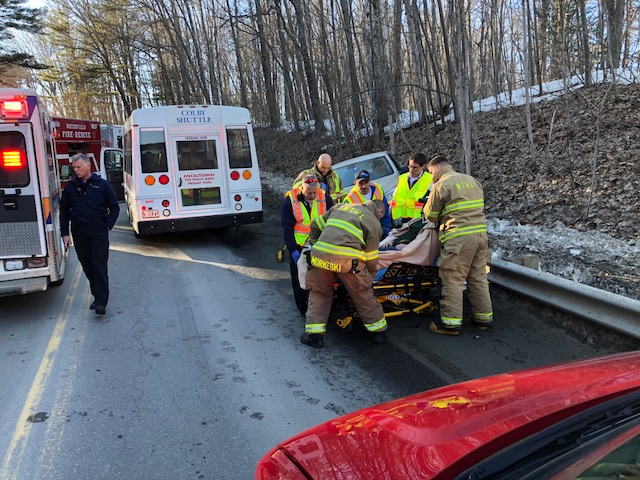 Emergency responders tend to the driver of a Chevy sedan that collided with a Colby College shuttle on North Street Hill on Monday.