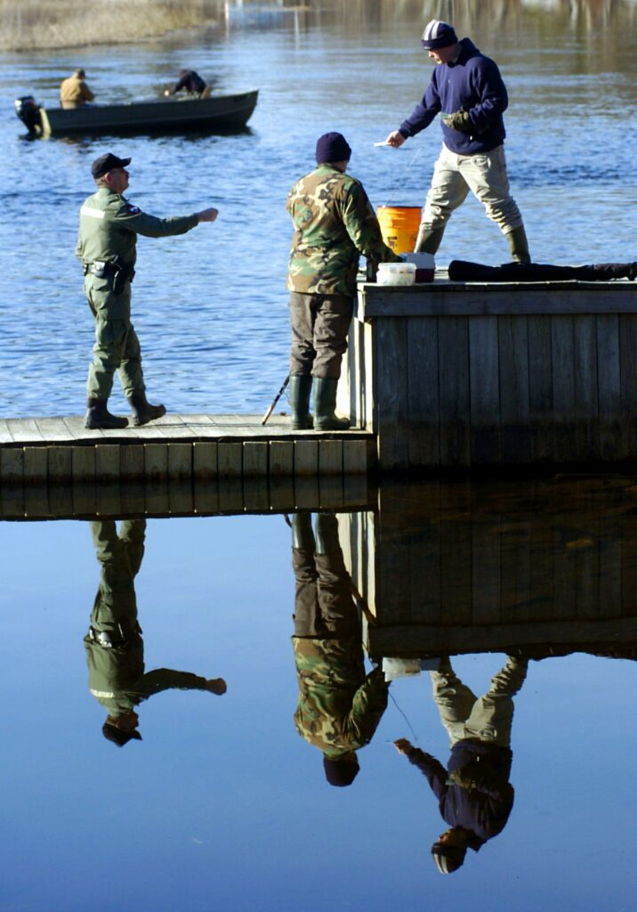 Tom Hujara, right, of Oakland, hands his fishing license to Game Warden Dan Murray, left, atop Wings Mills Dam in Belgrade in April 2007. Funding for maintenance of the dam and two others will be addressed at the Rome Town Meeting on Saturday.