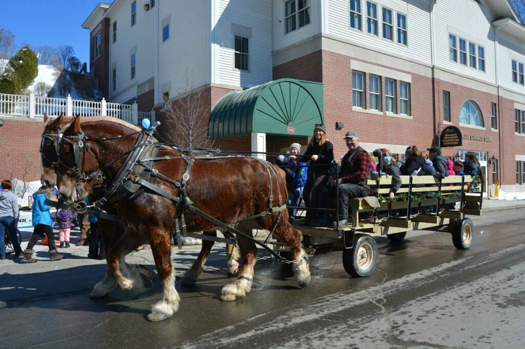 Kendric Charles, seated, is the horse driver during a previous Fire and Ice Festival in Farmington.