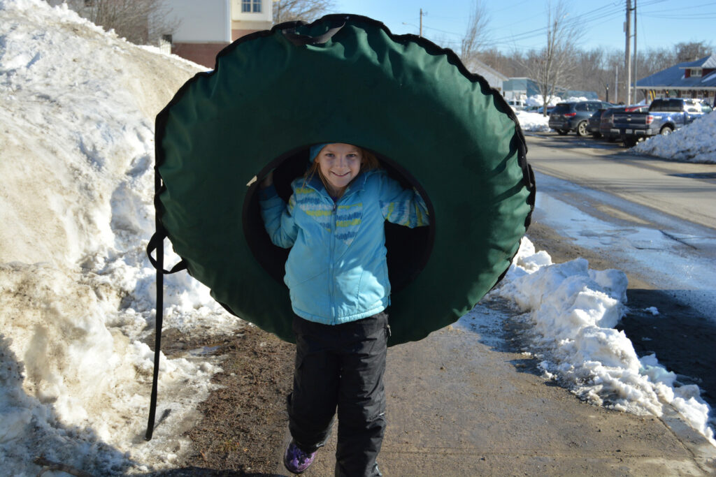 Avery Tinker carries a snow tube during a previous Fire and Ice Festival in Farmington. Those you don't have a snow tube, you can pick one up on Franklin Savings Bank's Front Street lawn during the festival.