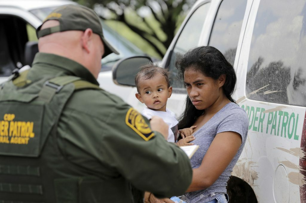 """A mother migrating from Honduras holds her 1-year-old child as she surrenders to Border Patrol agents after illegally crossing into the U.S. on Monday near McAllen, Texas. Confusion rose Monday over the Trump administration's """"zero-tolerance"""" policy."""